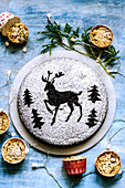 Chocolate cake dusted with icing sugar through a stencil of deer and Christmas trees