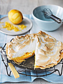 Lemon merigue pie slice out and with grated lemon zest