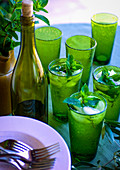 Mint iced water in green glasses on table