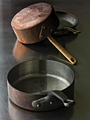 Old copper pans on stainless steel surface