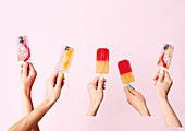 Hands holding exotic fruit ice popsicles