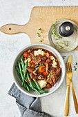 Slow cooker beef brisket bourguignon with mashed potatoes and beans