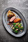 Duck breast with a slice of potato and pumpkin tart, and almond-broccoli