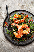 Flambéed king prawns on sea asparagus