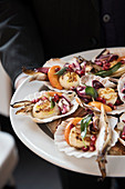 Scallops with radicchio, chicory, herbs and pomegranate seeds in shells