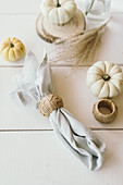 Autumnal arrangement of pumpkins and linen napkins with cane napkin rings on table