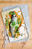 Asian trout with vegetables on a roasting tray