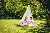 Zwei Freundinnen sitzen unterm DIY-Baldachin im Garten