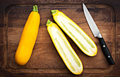 Two yellow courgettes, one whole and one halved