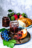 Grape and fig confiture, fresh blue grapes and bun with confiture