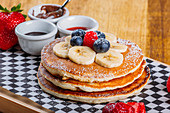 Delicious fried fluffy pancakes with icing sugar and fresh berries served for breakfast