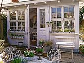 Kies - Terrasse mit Frühlingsblumen am Gartenhaus