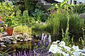 Gartenteich mit Sumpfpflanzen an der Terrasse