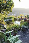 Kleine Terrasse mit Adirondack-Sessel am Gartenteich