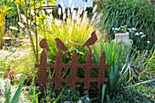 Federborstengras 'Hameln' hinter Dekozaun aus rostigem Eisen