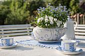 Suppenterrine mit Vergißmeinnicht und Hornveilchen als Tischdekoration