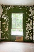 Abblätternde grüne Wandfarbe im verfallenen Raum
