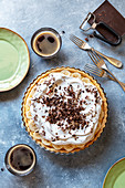 Banana cream pie decorated with chocolate curls and 2 cups of coffee on the table