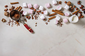 Ingredients for hot chocolate: White pink big marshmallow, cocoa beans, cocoa powder, cinnamon, chopped chocolate and nuts