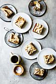 Mehrere Stücke Bananenkuchen mit Butterscotch auf Tellern (Aufsicht)