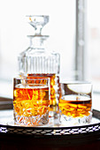 Whiskey in a tumbler alongside a cut glass decanter
