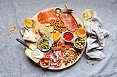 Chacuterie-Platte mit Wurst, Käse, Knabbereien und Weißwein (Aufsicht)