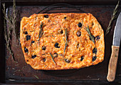 Unleavened bread made with cheddar cheese, rosemary and olives on a wire rack
