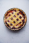 Berry pie with a lattice decoration on concrete background