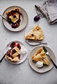 Mehrere Stücke Beeren- und Apfelpie auf Tellern serviert mit Eis