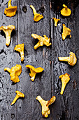 Chanterelle mushrooms on a dark wooden surface