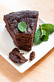 A slice of cocoa and aubergine purée cake with mint leaves