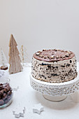 A chocolate cake on a cake stand on a table decorated for Christmas