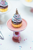 Muffins with pastel coloured frosting decorated with unicorn horns