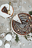 A sliced chocolate cake on a table decorated for Christmas (seen from above)