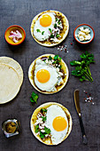 Corn tortillas with fried eggs, pesto sauce and feta cheese
