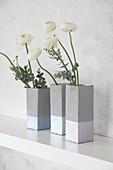 DIY-Vasen im Beton-Look aus Milchtüten mit Ranunkel auf Ablage
