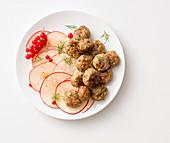 Pork meatballs on apple carpaccio