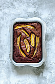 Brownie with milk chocolate, bananas and sea salt in aluminum form on a concrete surface