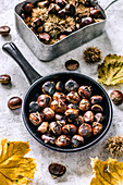 Roasted chestnuts in a frying pan, raw chestnuts, shelled and unshelled, yellow leaves