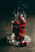 Cherries falling into a glass of iced water