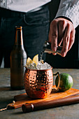 Moscow Mule (cocktail with vodka, ginger beer and lime) being made