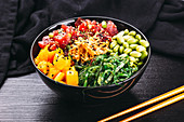 A poke bowl with tuna fish, mango, algae and edamame (Asia)