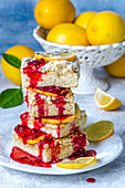 Lemon pie cut by squares, poured with raspberry sauce, decorated with lemon slices and fresh lemons