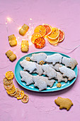 Gingerbread in the form of pigs on a blue plate sprinkled with powdered sugar, garland and citrus chips (2019 Year of the pig)