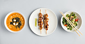 Japanese appetizers: miso soup, kebabs and a vegetable salad (seen from above)