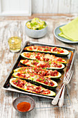 Baked courgette stuffed with sausage and tomatoes