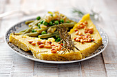 Polenta slices with pine nuts and beans
