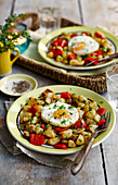 Fried potatoes with fried eggs and cherry tomatoes