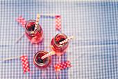 Drei Beerendrinks mit Strohhalmen in Flaschen