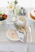 Place setting with linen napkin and name card on table set for afternoon coffee